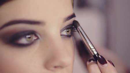 eyeshade : Make-up artist applying eye shadow makeup to models eye. Close up view. Smoky eyes. Left view Stock Footage
