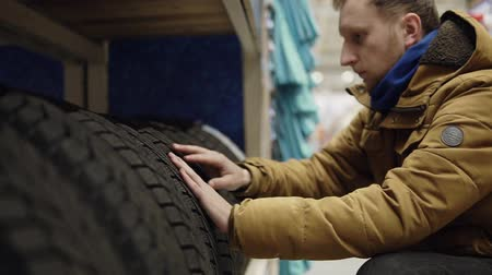 pneus : Man chosing new tires in shop
