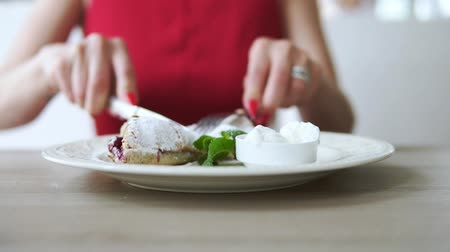 příbory : Unrecognizable girl in red dress eating dessert strudel at the restaurant using fork and knife. Slowmotion shot.