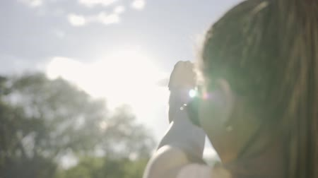 looking far away : Closeup back view of a woman looking at the sun and hiding herself from the sun with her hand. Young woman with dreads playing with a sunbeam. Slowmotion shot. Stock Footage