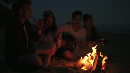 друзья : Picnic of young people with bonfire on the beach in the evening. Cheerful friends singing songs and playing guitar. Slowmotion shot