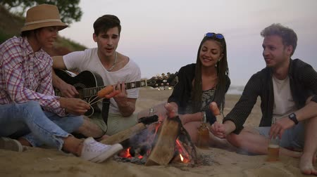 dospělý : Group of young and cheerful people sitting by the fire on the beach in the evening, grilling sausages and playing guitar. Slowmotion shot