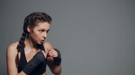 suor : Young woman training with her hands wrapped in boxing tapes isolated on grey background. Slowmotion shot