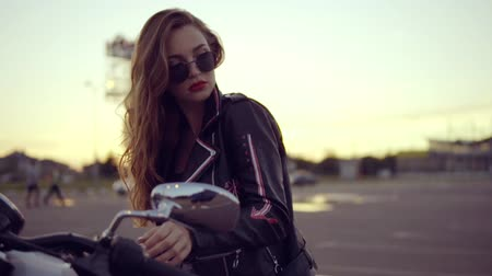 rebelião : Portrait of a female biker in leather jacket and shorts sitting on her bike and holding a handlebar. Close up of young sexy curly woman in sunglasses on the chopper Stock Footage