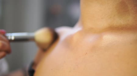 pędzel : Closeup view of a brush applying golden powder on the models neck and chest. Professional make up. Slowmotion shot