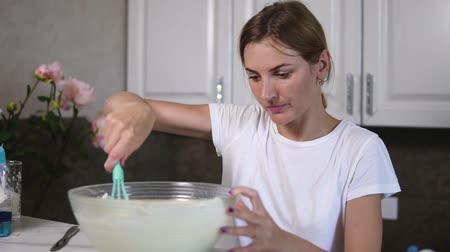mashing : Young woman prepares dough mixing ingredients in the the bowl using whisk in the kitchen. Homemade food. Slowmotion shot Stock Footage