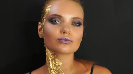 make photo : Closeup of a young woman standing on the black background and looking in the camera. Expressive and stylish golden makeup and hairstyle. Skin covered with golden metallic pieces