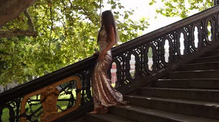 eleganckie : Attractive young fit woman in a long golden shiny dress walks down on the stairs on high-heels in summer. Party preparation, fashion model. Slowmotion shot Wideo