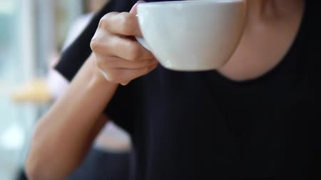 mozog e fel : Closeup view of female hands taking a white cup with hot tea from the wooden table. Then camera moves up with a cup and this woman starts to drink her tea. Slowmotion shot