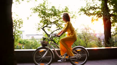 giydirmek : Brunette smiling woman in long yellow dress is enjoying her time riding a city bicycle with a basket and flowers inside during the dawn. Lens flare. Steadicam shot. Slowmotion Stok Video
