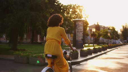 kolo : Back view of an unrecognizable woman riding a citybike with a basket and flowers in the city center during the dawn enjoying her time early in the morning. Lens flare Slowmotion shot