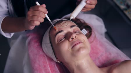 de sangue puro : Carboxytherapy for young woman in professional spa salon. Young woman is lying on the couch while professional cosmetologist is apllying special treatment on womans face using brush Stock Footage