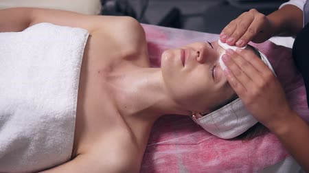 aydınlatmak : Professional cosmetologist is toning womans face using cotton sponge. Young woman is lying on the couch during cosmetic face procedure in spa salon. Face care. Beauty, healthy and youth concept