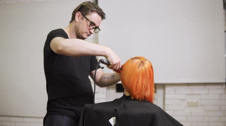 bob hairstyle : Close-up shot of a woman having her hair straightened by a male professional hair stylist in hair salon. Shot in 4k Stock Footage