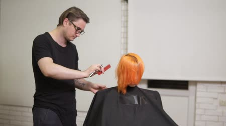 bob hairstyle : Stylish professional male hairdresser in glasses combing hair of female client in hair salon turning around her chair and looking at the results. Slowmotion shot