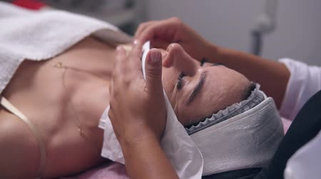 aydınlatmak : Closeup view of professional cosmetologist dab dry womans clean face skin using paper tissue. Young woman is lying on the couch during cosmetic face procedure in spa salon. Face care Stok Video