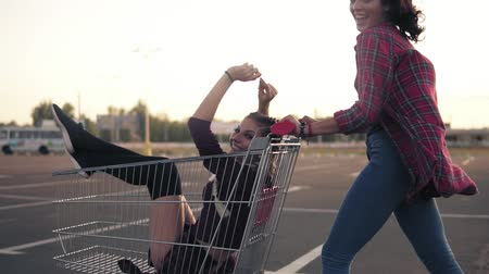 ostoba : Side view of a happy young woman pushing a grocery cart with her girlfriend inside in the parking by the shopping mall during sunset. Slowmotion shot Stock mozgókép