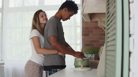 объятие : African man preparing food in pot standing in the kitchen. His caucasian girlfriend coming up to him and embracing. Real love. Slowmotion shot