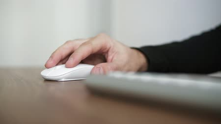 mansão : Side view of a young mans hand using wireless computer mouse sitting at the table in the office. Wooden table desktop. Shot in 4k Stock Footage