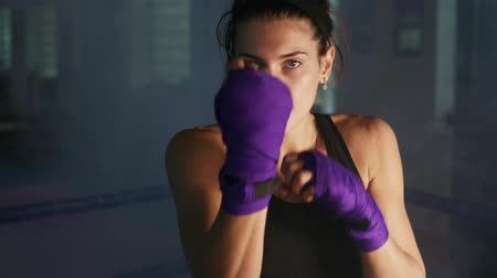кулак : Portrait of a young martial arts female athlete shadow boxing looking in the camera training in a dark room with smoke. Her hands are wrapped in bandage. Slowmotion shot Стоковые видеозаписи