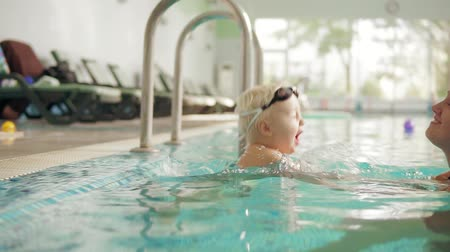 biztonság : Young mother is teaching her cute blonde toddler to swim in the swimming pool. She is sitting by the water then she helps him to dive. Cute child is wearing special protective glasses in the pool