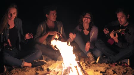atividades : Multiracial group of young women and men sitting by the bonfire late at night and singing songs, playing guitar and percussion
