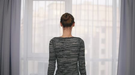unveil : Back view of young attractive woman opening curtains on a big window and letting the light in the room. Looking out the window. Slowmotion shot