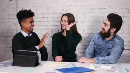 human hand : Multi-ethnic business team giving high five sitting at the table in modern office. Slowmotion shot