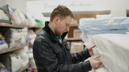 купить : Young man is choosing a mattress in a big furniture shop or supermarket. He is checking its elasticity, memory foam by pressing on it