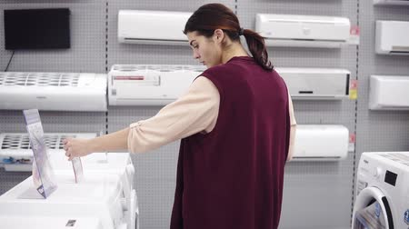 pricetag : Female costumer checking the pricetag while choosing washing mashine in appliance store. Buying new household equipment