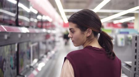 pricetag : Girl passing through row of TV screens in electronics store looking for mew home electronics. Stock Footage