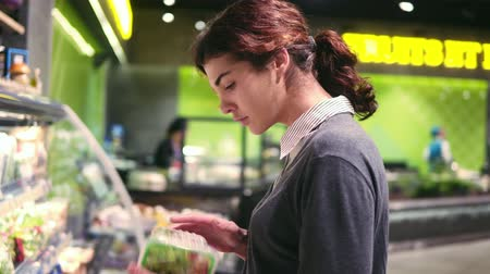 решить : Young beautiful brunette girl in her 20s trying to choose prepacked salad leaves in a grocery store. Стоковые видеозаписи