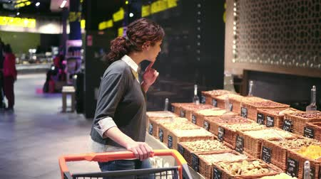 решить : Young girl trying to choose nuts in a supermarket. Buyer asking for help