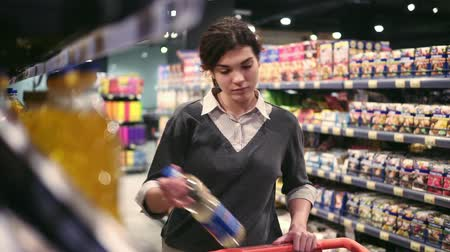 comparar : Young beautiful female costumer choosing oil in local grocery store.