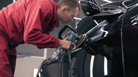 престиж : Man in red work suit polishing black car at autocenter.