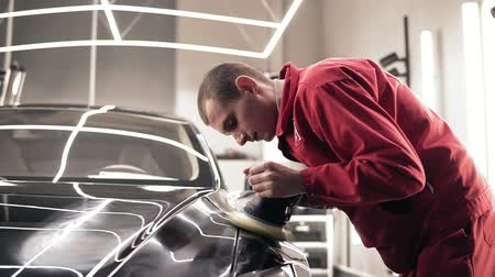 prestiž : Hardworking male autocenter represantative polishing intensly new black car.