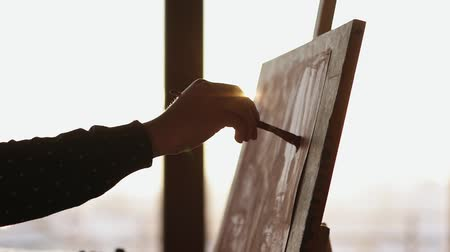artistas : Female hand drawing with paint on canvas that is placed on easel.