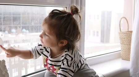 darling : A little girl is sitting on the windowsill, the cat is looking at her from the floor