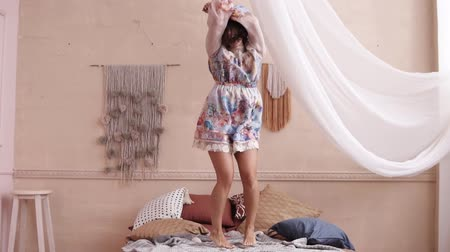 ベッドルーム : Happy woman jumping on her bed in a cute floral dress. Room with a white curtain. Front footage 動画素材