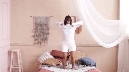 svetr : Beautiful brunette female jumping on bed in white shorts and jumper. Onward footage
