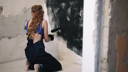 decorating : Beautiful woman on her knees paints with pressure white wall