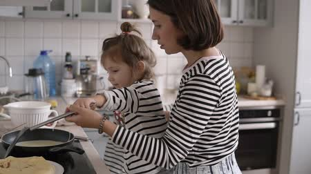identical : Young stylish mother helps daughter turn the pancake with a shovel and having fun while cooking together in kitchen at home with two children Stock Footage