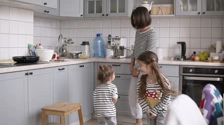 identical : Funny, young and cheerful mother is playing with daughters. Imitating horse riding using shovels in the kitchen while cooking