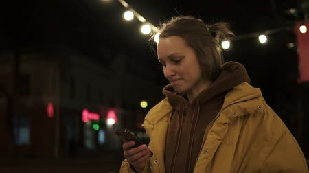 plavé vlasy : Pretty girl in the middle of a dark street with lights looks at the phone and smiles. Yellow coat. Side view
