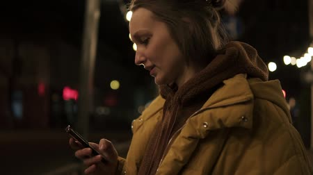 ярмарка : Short haired girl walks through the evening city smiling, stops and texting in the smartphone. Handheld footage Стоковые видеозаписи