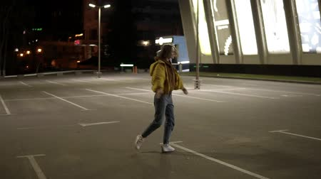 ярмарка : Slim, delicate girl in grey pants and yellow coat is dancing and has fun on the parking outside