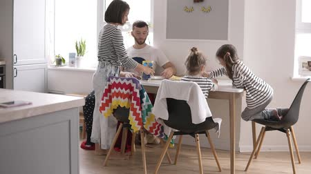 kahvaltı : Happy young family taking breakfast together in the white kitchen at home with little children. Eating pancakes Stok Video