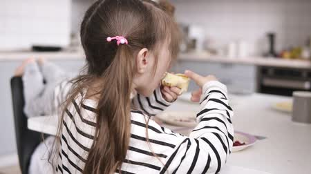 panqueca : Two little sisters eat pancakes at the table with father behind them. Side view Stock Footage