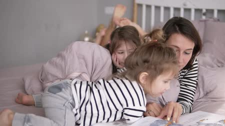 identical : Young mother is reading a tale for her lovely little daughters lying on a bed. Little one is looking through the book. Close up Stock Footage