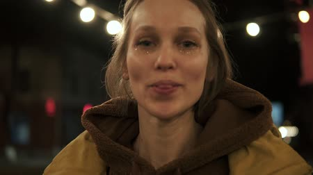 plavé vlasy : Front footage of young girl on the night street smiling and playfully sticking out tongue. Street lights behind